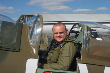Comedian Al Murray sitting in Supermarine Spitfire at Duxford