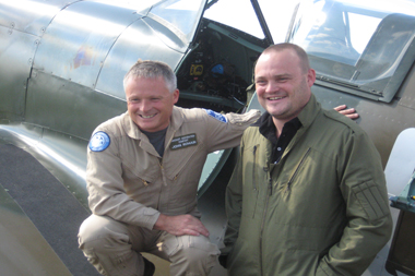 Comedian Al Murray and John Romain (Aircraft Restoration Company) with two-seat Supermarine Spitfire at Duxford